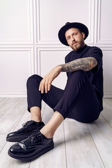 Fashionable tattooed guy in studio on white