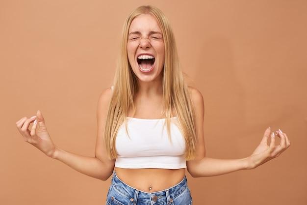 금발 머리를 가진 유행 십 대 소녀는 청바지와 흰색 탑 소리를 착용