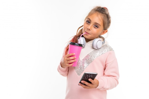 Fashionable teenager girl in pink hoody plays in phone games