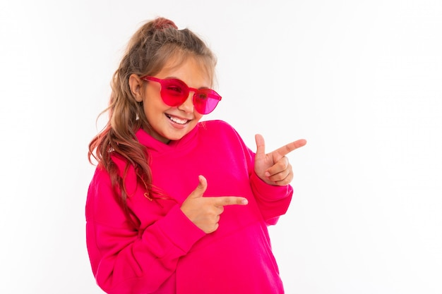 Fashionable teenager girl in pink hoody and with pink sunglasses gesticulates