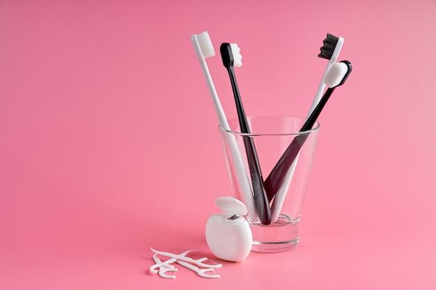 やわらかい毛のファッショナブルな歯ブラシ。人気の歯ブラシ。衛生動向。口腔衛生キット。ピンクの背景にガラス、フロス糸、つまようじの歯ブラシ。