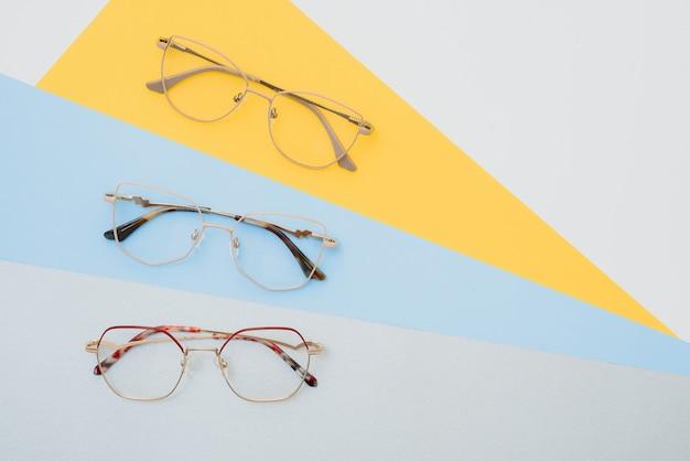 Модные ультрамодные очки для коррекции зрения на разноцветном фоне, геометрический фон из бумаги пастельных тонов.