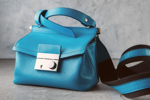 Fashionable turquoise crossbody bag on the gray concrete background.