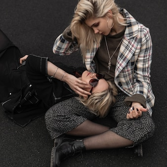Fashionable two sexy modern girlfriends with blond hair in casual youth trendy clothes rests on asphalt on summer day. stylish attractive girls in vintage clothing