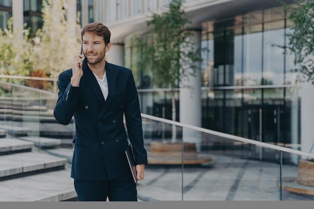 Модный небритый бизнесмен использует современные технологии, телефонный разговор держит гаджет