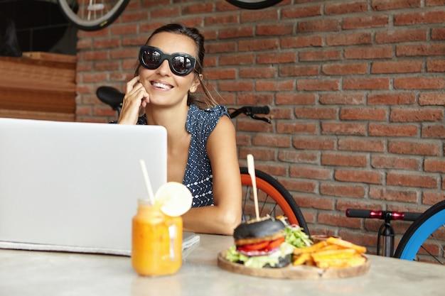 Модный видеоблогер в стильных солнцезащитных очках, записывающий видео с веб-камеры на портативном пк, сидя у стены из красного кирпича современного кафе. счастливая женщина с красивой улыбкой, серфинг в интернете на портативном компьютере
