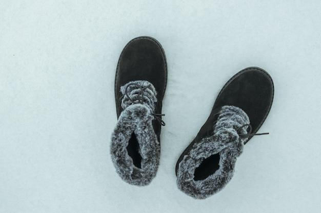 눈 덮인 배경에 세련된 따뜻한 여성용 신발. 아름답고 실용적인 여성용 겨울 신발.