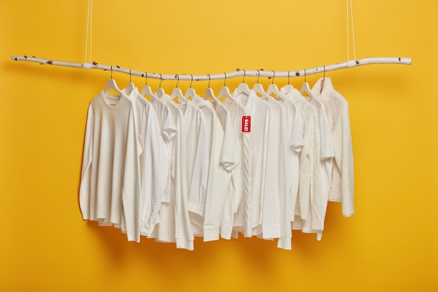 Fashionable white clothing on hangers with red tag inscriped sale, hanging on wooden rack against yellow background, copy space.