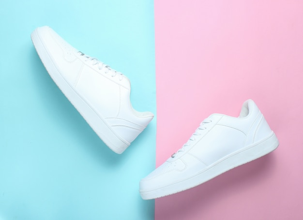 Fashionable white sneakers on a colored pastel table, minimalism, top view, creative layout, step