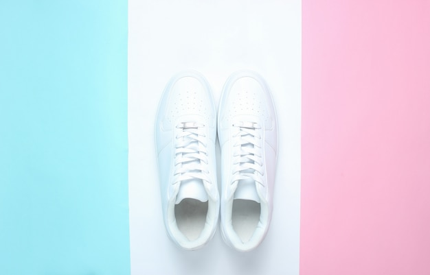 Fashionable white sneakers on a colored pastel table, minimalism, top view, creative layout