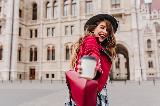 Donna bianca alla moda che posa con la tazza di latte sulla parete di architettura