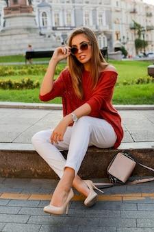 Donna bianca alla moda in maglione che si siede sulla strada nel centro della città. occhiali da sole alla moda. umore autunnale.