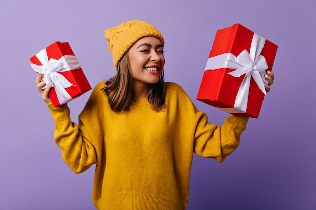 Fashionable white woman waiting for christmas. portrait of pleased brunette girl with red new year presents.