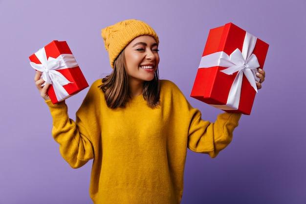 Donna bianca alla moda in attesa del natale. ritratto di ragazza bruna soddisfatta con regali rossi di capodanno.