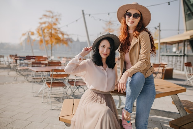 Fashionable woman in beige hat sitting on table during photoshoot with friend