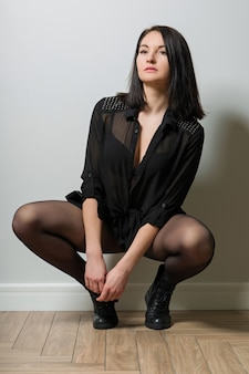 Fashionable woman in black tights on legs and stylish leather boots