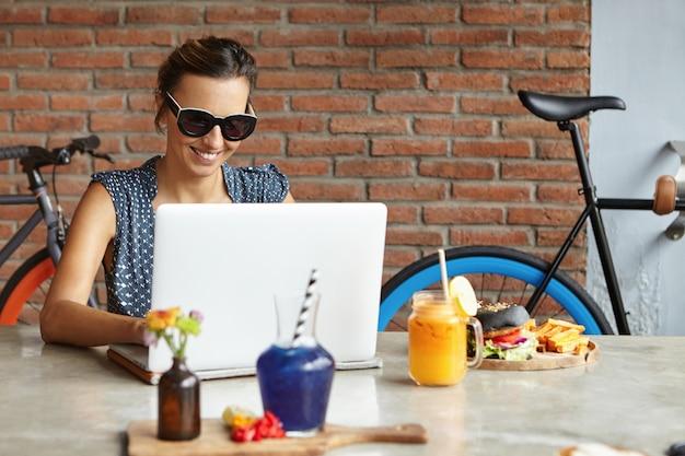 Модная женщина-блоггер пишет новый пост на портативном компьютере, используя высокоскоростное интернет-соединение во время обеда