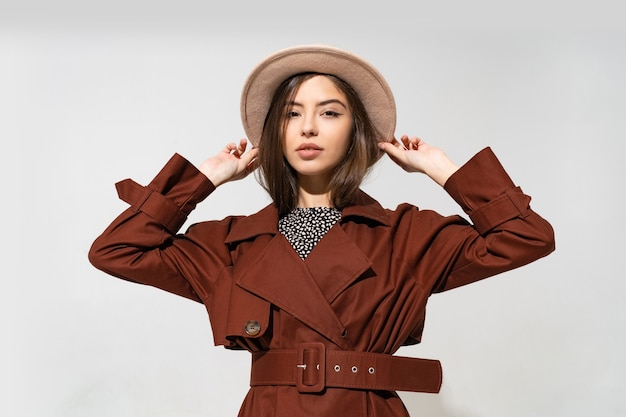 Fashionable woman in brown  coat and  beige hat posing