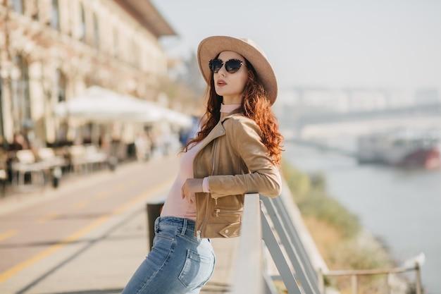 Donna alla moda in jeans casual che gode del servizio fotografico sulla parete del fiume