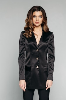Fashionable woman in classic black suit made of silk.