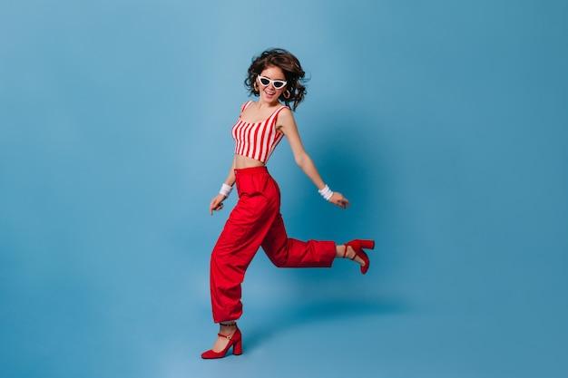 Donna alla moda in vestiti in stile anni '80 corre sulla parete blu