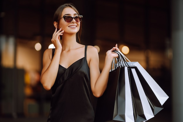 Fashionable woman dressed in a black dress with shopping bags.