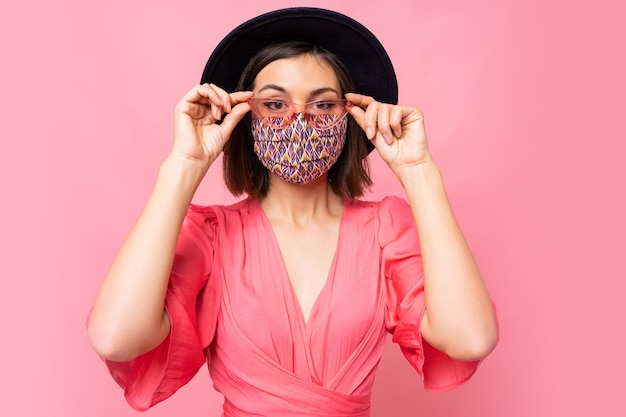 유행 여자 옷 보호 세련된 얼굴 마스크. 검은 모자와 선글라스를 쓰고. 분홍색 벽 위에 포즈