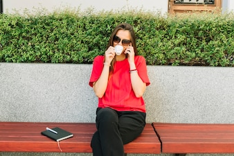 Fashionable woman drinking cup of coffee talking on cellphone