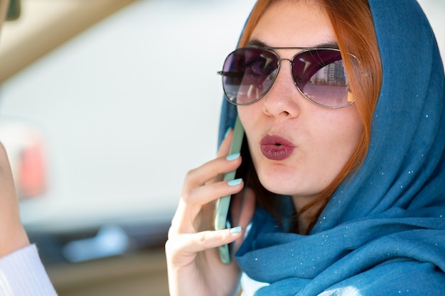 Fashionable woman driver in scarf and sunglasses talking on mobile phone while driving a car.