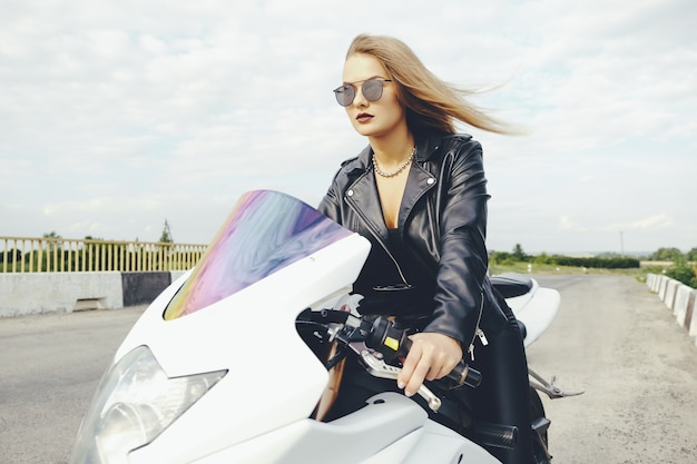 Fashionable woman driving a bike on a road