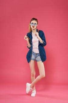 ファッショナブルな女性のフルレングスベースのバックパックサマースタイルピンクの背景