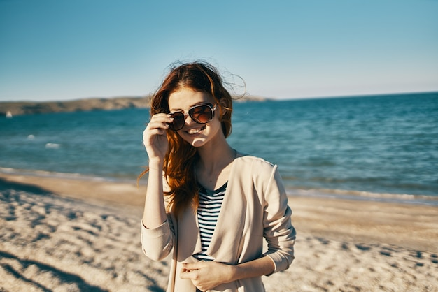 Fashionable woman in glasses and in a beige coat on the seashore in the mountains closeup portrait