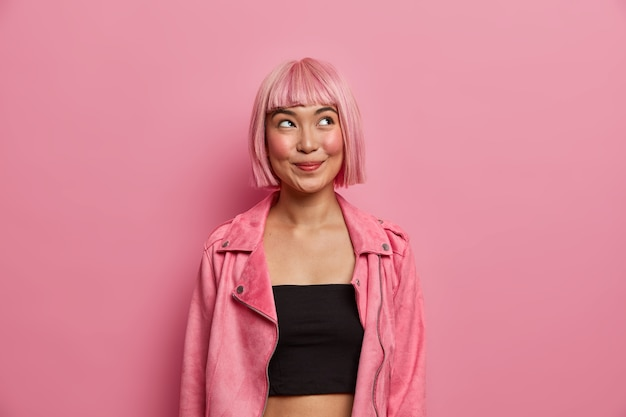 Fashionable woman has bobbed pink hair and fringe, looks with happy dreamy expression, tempting look up, wears black top with stylish rosy jacket. pleasant emotions, style concept