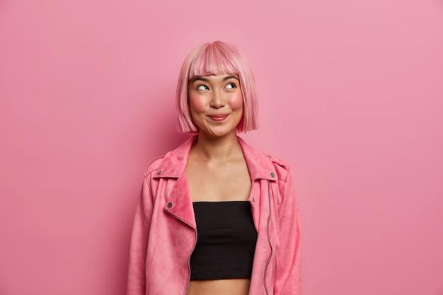 La donna alla moda ha i capelli e la frangia rosa ondulati, guarda con un'espressione felice e sognante, guarda in alto allettante, indossa un top nero con una giacca elegante e rosea. piacevoli emozioni, concetto di stile