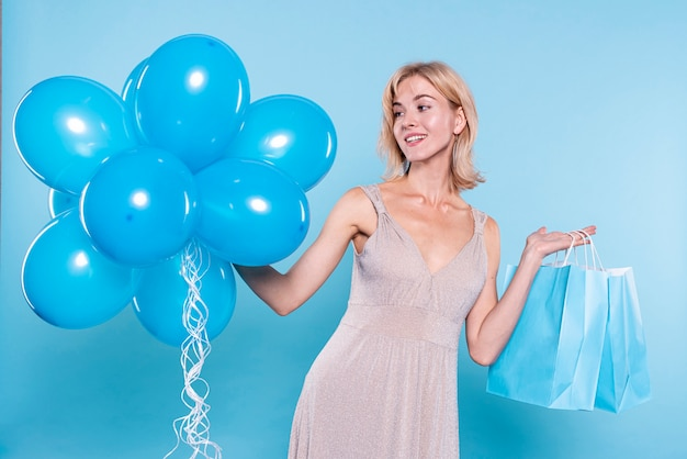 Fashionable woman holding balloons and gifts bag