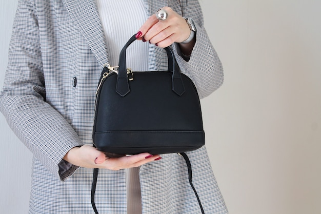 Модная женщина, держащая черную кожаную сумку. место для вашего текста