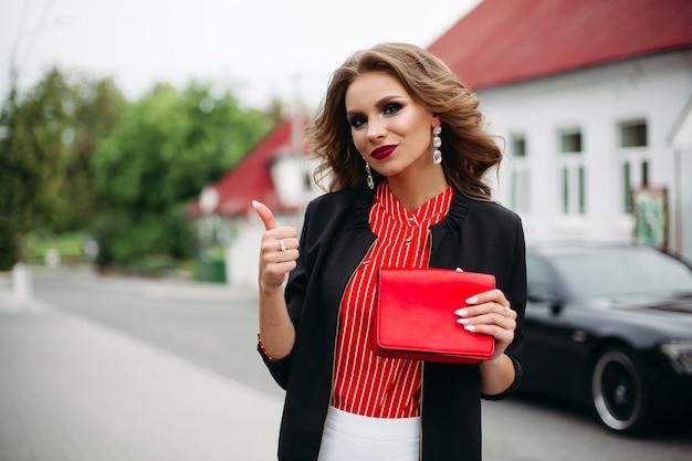 유행 여자 빨간 clatch를 잡고 손가락으로 슈퍼를 보여주는.