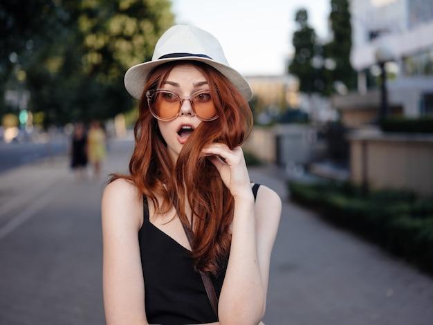黒いドレスと白い帽子をかぶったファッショナブルな女性は、通りの自然の中で休んでいます