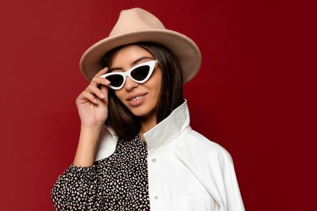 Модная женщина в шляпе, платье и белой куртке, позирует. модный зимний образ.