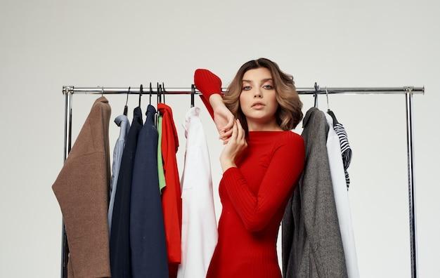 赤いセーターを着たファッショナブルな女性が、ショッピングシャツの服を着たワードローブの近くに立っています。