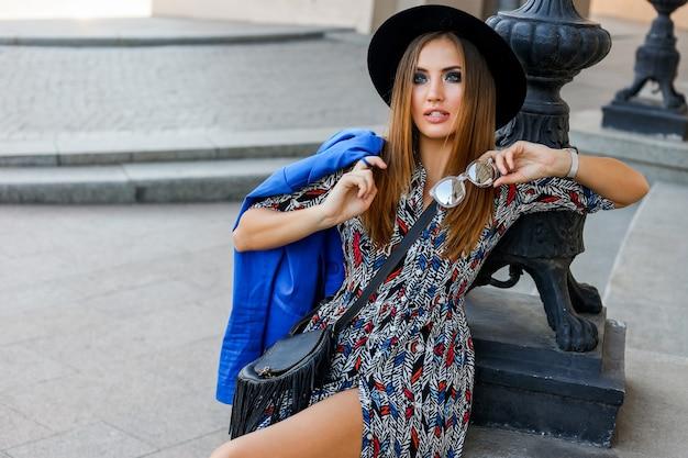 黒い帽子、青いジャケット、エレガントなドレスを着たファッショナブルな女性。古いヨーロッパの都市でポーズをとる。