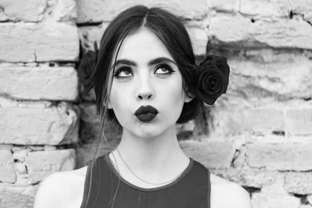 レンガの壁の背景に髪のバラと真っ赤なドレスのファッショナブルな女性