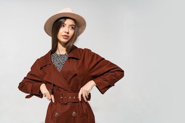 Модная женщина в коричневом пальто и бежевой шляпе позирует