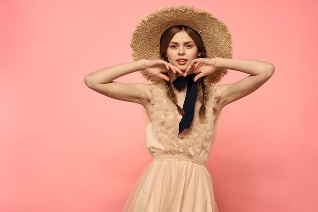 モデルの感情の楽しみのピンクのクロップドビューに黒いリボンとドレスと帽子のファッショナブルな女性。