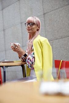 屋外でコーヒーを飲むメガネのファッショナブルな女性