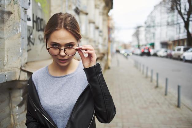 屋外で革のジャケットを着たファッショナブルな女性はライフスタイルを歩きます。高品質の写真