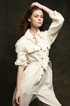 暗い背景のスーツの服のスタイルで明るいオーバーオールのファッショナブルな女性