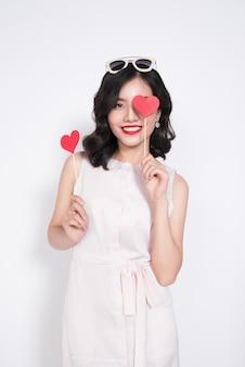 Модная женщина в красивых платьях держит красную форму сердца.