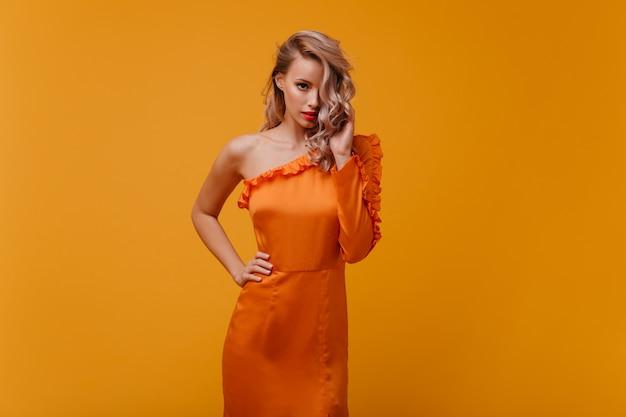 正面を向いているオレンジ色のドレスのファッショナブルな女性