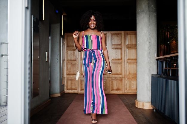 Модная женщина в розовом полосатом комбинезоне